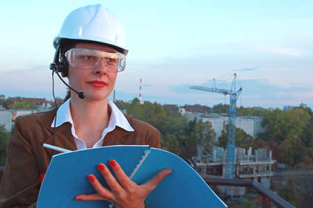 Female engineer manages building operations and records important data photo