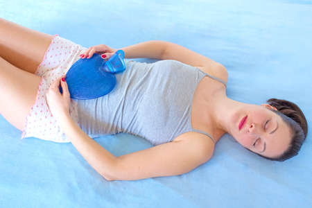 A young woman holding a water bottle on her stomach to alleviate stomach problems, photography Фото со стока