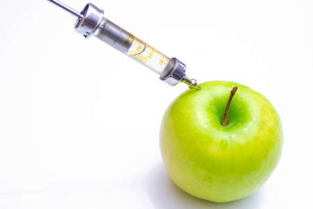 food photography: GMO apple injection with syringe on the white background, Genetically modified food, photography