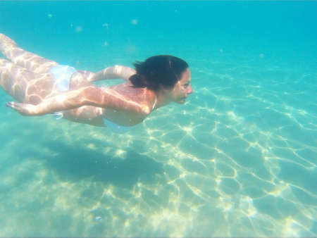 Young woman diving in beautiful blue sea, Photography