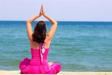 Beautiful young woman is doing exercises yoga on the seashore, Photography