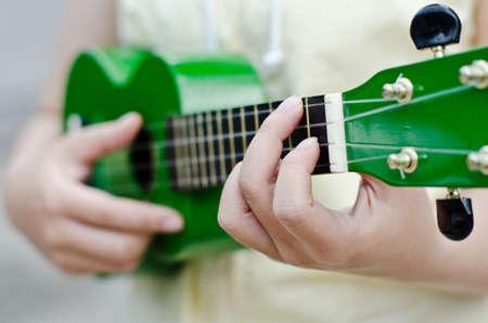 Closeup of a woman playing ukulele
