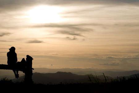 Una niña con puesta de sol en la montaña en la silueta Foto de archivo