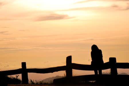 mujer mirando el horizonte: Una chica con puesta de sol en la montaña en la silueta