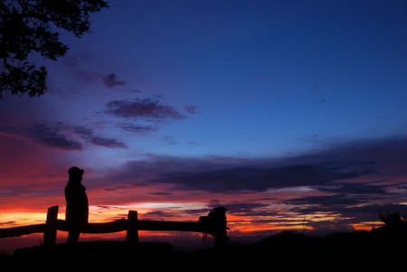 A girl with sunset on the mountain in silhouette