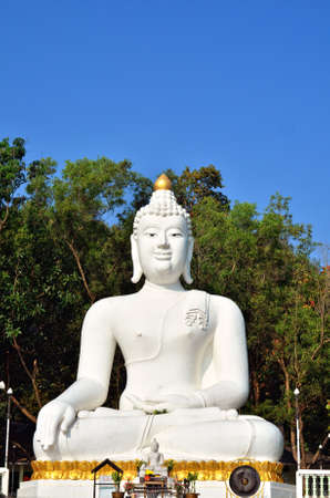 Gold Buddha statue over blue sky  photo
