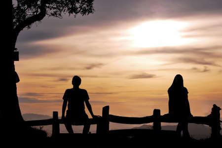 mujer mirando el horizonte: Silueta de la muchacha y el hombre en la colina