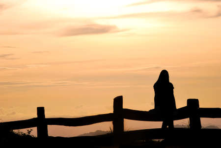serene people: silhouette girl on the hill
