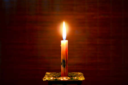Burning candle on candlestick, a dark background photo