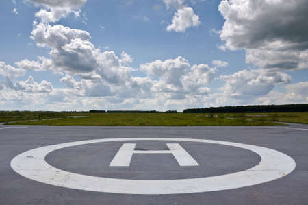 helideck: Helipad in the field in cloudy day. Stock Photo