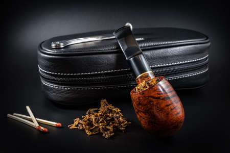 Smoking tube, tobacco, matches and case on a black background 2018