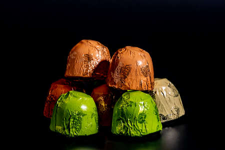 Chocolates in foil wrapper on black background