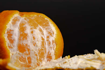 Half peeled mandarin on a black background close-up