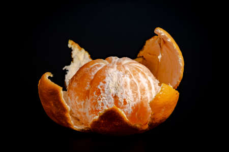 Half peeled mandarin on a black background close-up