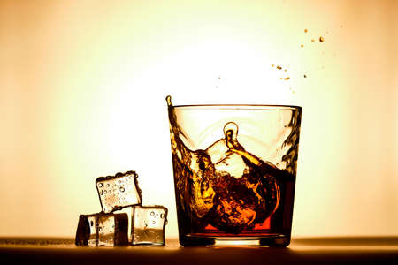 Ice cubes next to a glass of whiskey