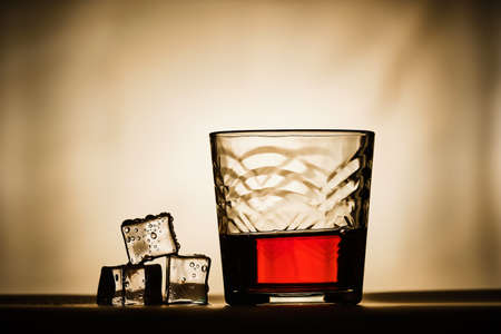 Ice cubes next to a glass of whiskey Imagens - 122583216