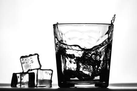 Ice cubes next to a glass of whiskey Imagens - 122583219