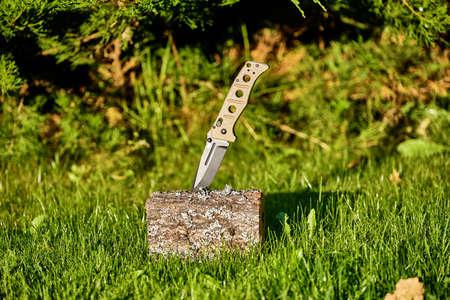 Folding knife on a stump on a background of grass