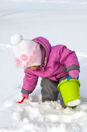 looking at baby: Little girl playing with snow