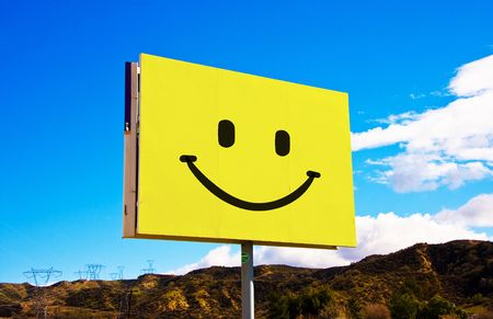 Yellow roadside billboard with smiley on the sky background