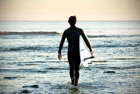 picture of a young surfer walking on the water