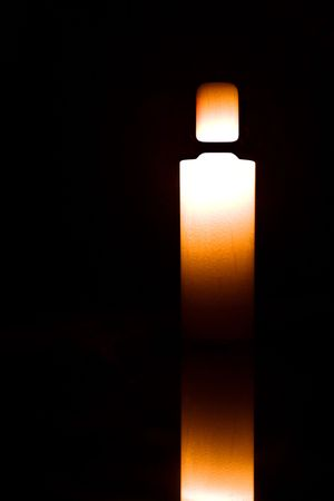 Light candle in form of perfume bottle isolated on black
