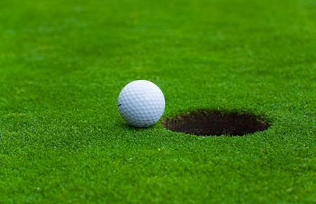 1 object: picture of a golf ball near the hole Stock Photo