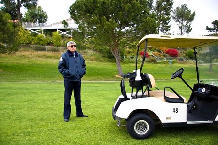 Picture of a security guard standing near the cart on the golf field