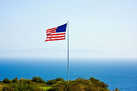 American flag on the hill close to the ocean photo
