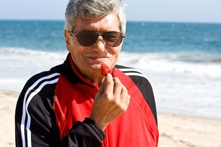 Old men eating a strawberry on the seashore