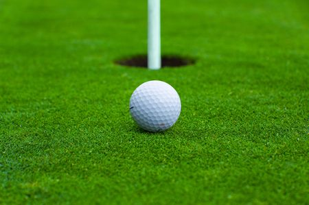 Picture of a golf ball close to hole with pole
