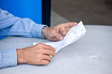 a man reading a bill in his hands Stock Photo