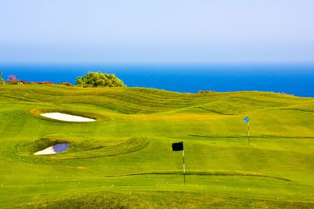 picture of a golf field over the sea photo