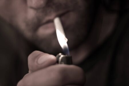 Man with cigarette and lighter ready to smoke Stock Photo