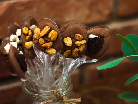 Chocolate desserts with almond and other goodies made on plastic spoons