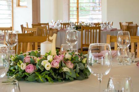 Hochzeitstischdekoration mit Blumen, Kerzen und Zahlen