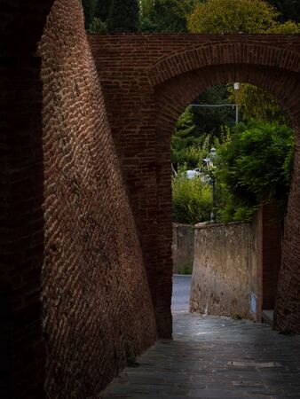 A narrow passage between two red brick walls in an old medieval Italian city with a beautiful view Stock Photo
