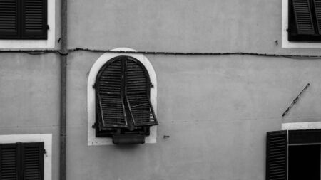 A window with semi opened blinders on a wall