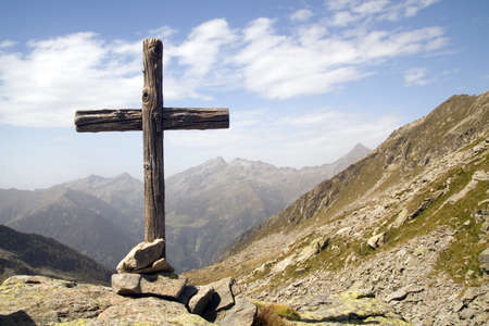 Wooden cross standing in italian Alps photo