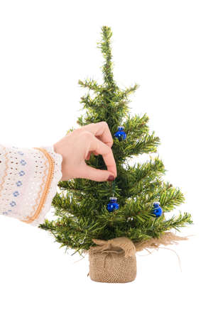Womans hand hangs blue christmas ball (isolated on the white) photo