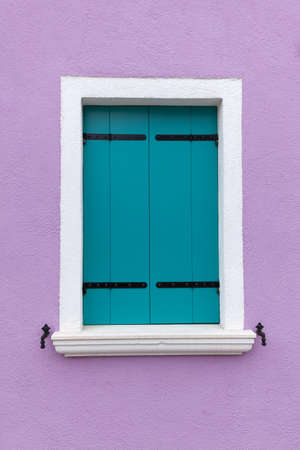 Picturesque old window with light blue shutters on light violet wall (Burano island, Venice, Italy)