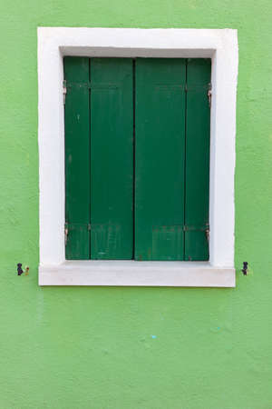 light green wall: Picturesque old window with dark green shutters on light green wall (Burano island, Venice, Italy)