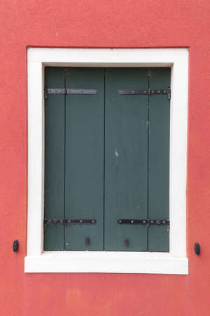 red shutters: Picturesque old window with dark shutters on red wall (Burano island, Venice, Italy)