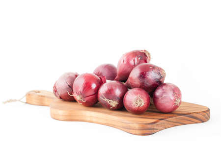 trencher: Bunch of red onions on wooden cutting board isolated on white background