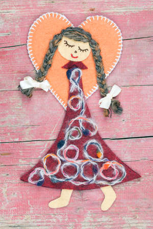 sewn: Sewn angel doll on pink wooden background Stock Photo