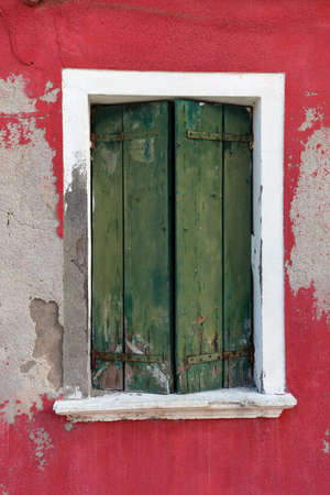 red shutters: Picturesque old window with green shutters on red wall (Burano island, Venice, Italy)