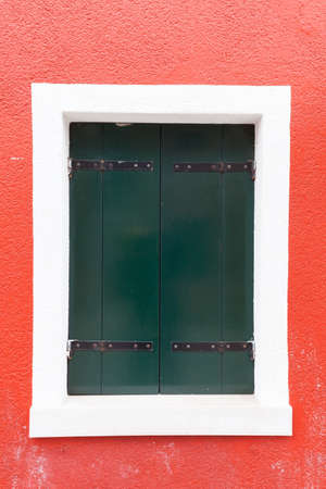 red shutters: Picturesque old window with dark green shutters on red wall (Burano island, Venice, Italy) Stock Photo