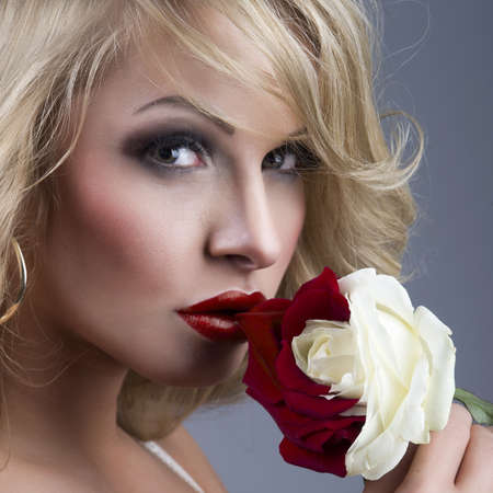close-up portrait of beautiful blonde woman with red - white rose photo