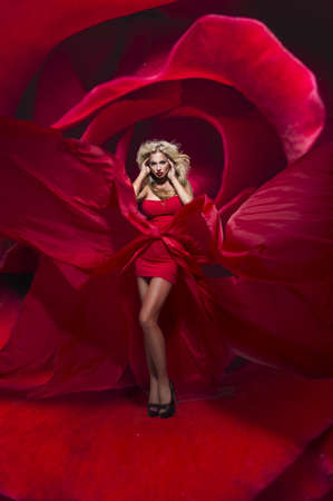 dress blowing in the wind: Beautiful young lady in red dress stands on flower rose Stock Photo