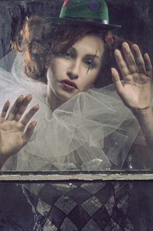 pierrot: Sad Pierrot woman behind the glass Stock Photo